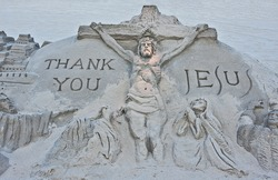 A sand sculpture on a beach of the crucifixion of Jesus