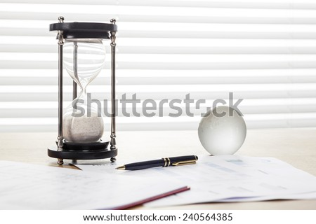 A sand timer(hour glass), glass globe, pen, graph paper(document) on the wooden office desk(table) behind white blind.