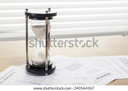 A sand timer(hour glass), graph paper(document) on the wooden office desk(table) behind white blind.