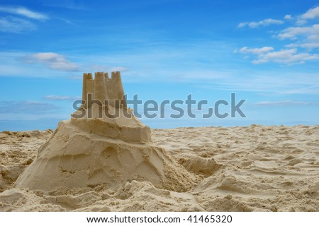 A sandcastle on a sandy beach, set against a bright blue summer sky.