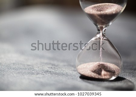 A sandglass, modern hourglass or egg timer with shadow showing the last second or last minute or time out. With copy space. #1027039345