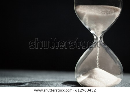 A sandglass, modern hourglass or egg timer with shadow showing the last second or last minute or time out. With copy space.