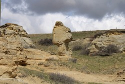 A sandstone hoodoo standing on a narrow base in Writing-On-Stone Provincial Park. Alberta, Canada.