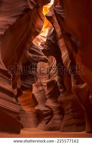 A sandstone rock formed cave with sandy floor showing sun shining through at the top.