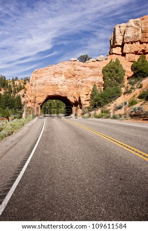 A sandstone tunnel marks the entry to Bryce Canyon National Park region in Utah's Red Canyon.