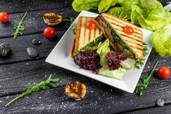 a sandwich with beef cheese and lettuce sliced lies on a plate with cherry tomatoes on a dark board fot