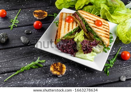 a sandwich with beef cheese and lettuce sliced lies on a plate with cherry tomatoes on a dark board fot  Stock fotó ©