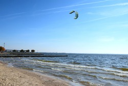 A sandy beach with a lake nearby and strong waves visible due to a strong wind with a single kite visible in the air and a concrete pier with some trees to be seen in the background in Poland