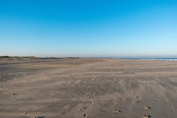 A sandy shore full of footprints under the blue sky in Norderney