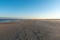 A sandy shore with footprints under the blue sky in Norderney