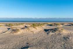 A sandy shore with grass on a sunny day in Norderney