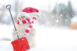 a santa doll in a red hat carrying a shovel in the snow