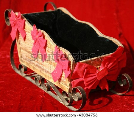 a santa sled with red bows on a red velvet background