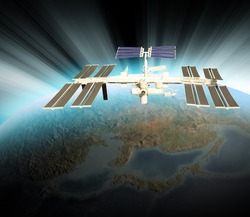 A satellite is above the Earth and is orbiting the planet. There is a white blue glow from the sun on the horizon. Use it for a space or technology theme.