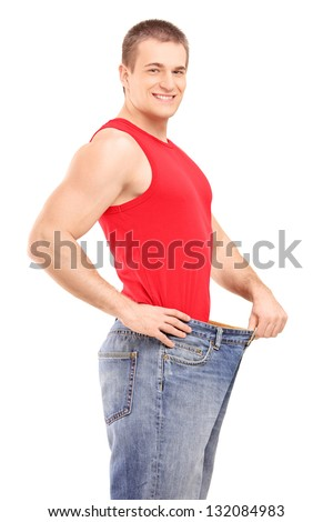 A satisfied weight loss man in a pair of old jeans isolated on white background