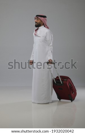 A saudi person traveling and pull out a travel bag on white background   Foto d'archivio ©