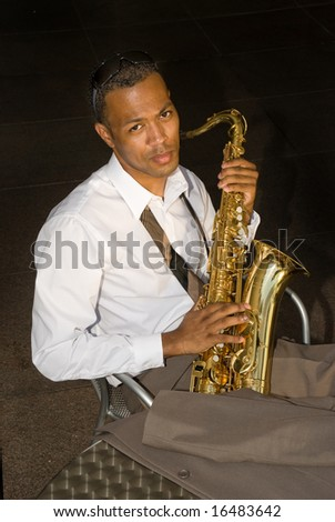 A saxophone player rests between songs. - stock photo