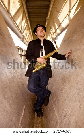 A saxophonist plays outdoors in an industrial setting.