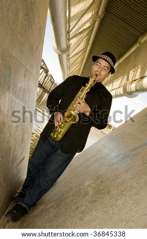A saxophonist plays outdoors in an urban setting under a bridge.