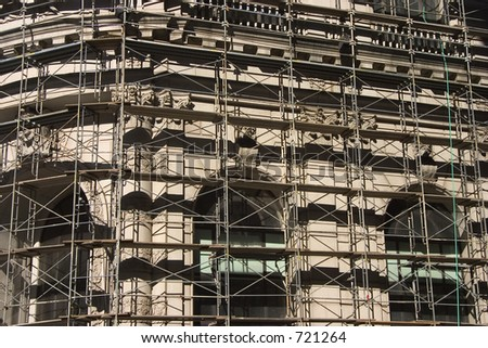 A scaffolding covers the classic stylings of an old building.