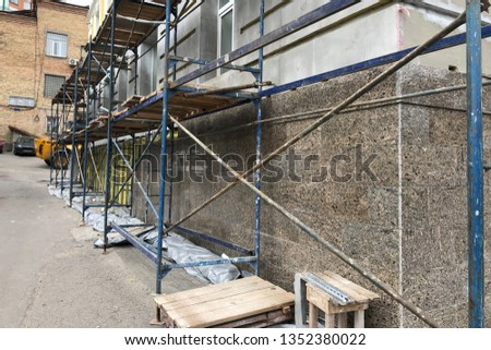 a scaffolding near the wall of the house under reconstruction. reconstruction of the old city buildings