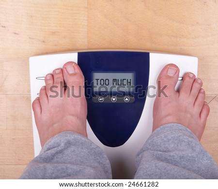 "A scale with two feet of the person standing on it on a wooden floor. The scale says: ""TOO MUCH""."