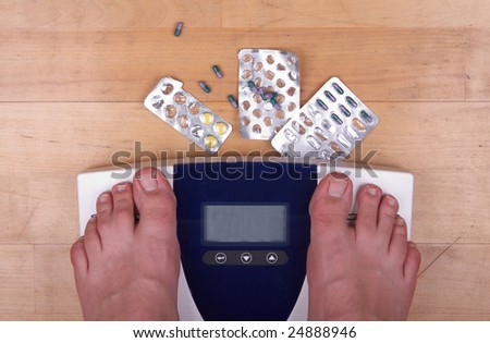 A scale with two feet of the person standing on it - on a wooden floor with pills to loose weight. The scale display is empty - copyspace.