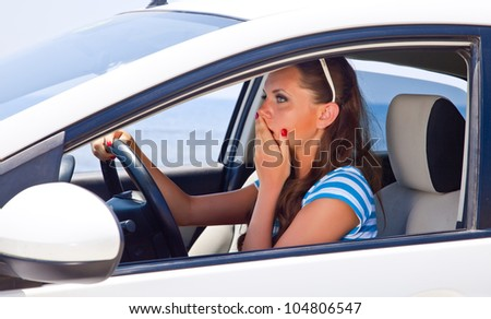 A scared beautiful woman is in the car