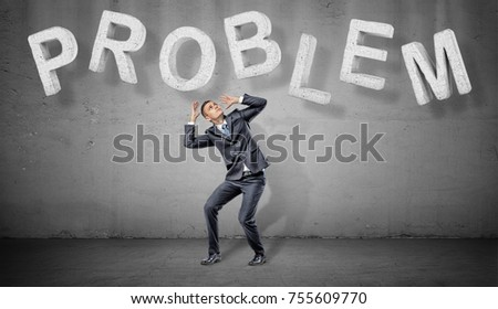 A scared businessman hides under large concrete letters making a word PROBLEM above him. Business and success. Weight of problems. Resolve all problems. #755609770