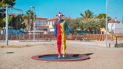 a scary clown wearing a colorful yellow, red and blue costume, bouncing on a trampoline in an outdoor public playground