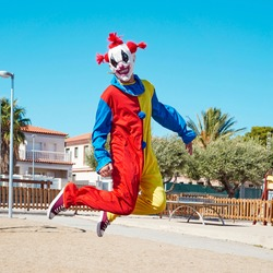 a scary clown wearing a colorful yellow, red and blue costume, jumping in an outdoor public playground