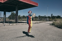 a scary clown wearing a yellow, red and blue costume, holding a golden balloon in his hand and jumping in front of an abandoned filling station