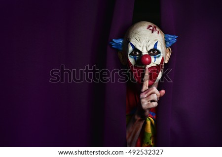 Photo of  a scary evil clown peering out from a purple stage curtain, with his forefinger in front of his lips, asking for silence, with a negative space on one side