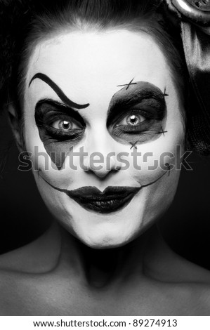 scary female clown staring from the dark - stock photo