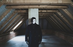 A scary guy in white mask with black hair and long dark coat standing in an abandoned attic. Scary and mystical picture. Horror concept.