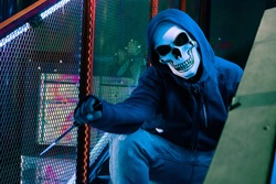 A scary murderer wearing skull mask and holding knife sitting in dark place. Horror and Halloween Concept.