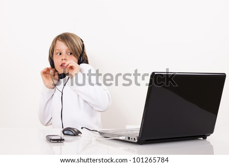 A scary young boy with a headset looks something on the Internet.