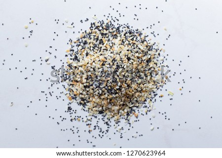 A scattered pile of Everything seasoning containing dried garlic, onion, poppy seeds, sesame seeds and salt on a white background.