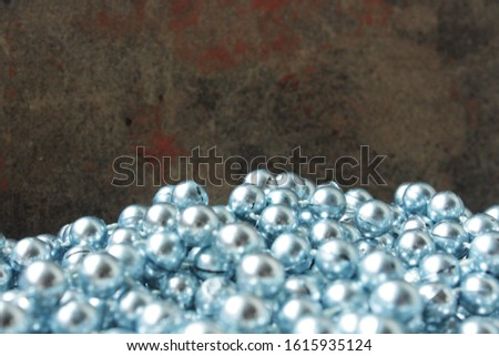 A scattering of blue beads on a background of a beautiful dark marble surface. Background surface for decoration