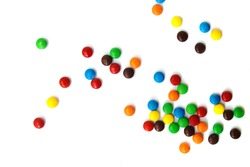 A scattering of colored small chocolates on a white background.Small colored candies