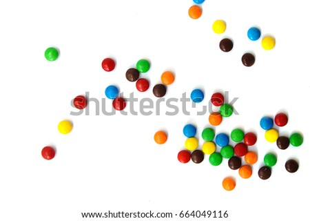 A scattering of colored small chocolates on a white background.