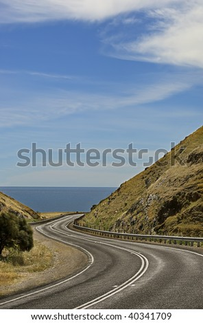 A scenic and winding coastal road between mountains, leading to the ocean.