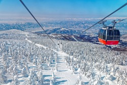 A scenic cable car flying over a piste in Zao hot spring & ski resort with a view of Juhyo (ice trees or snow monsters) all over the slope under blue clear sky on a sunny winter day in Yamagata, Japan