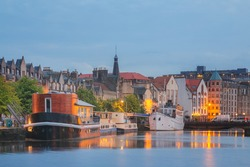 A scenic cityscape at night of the Leith Shore, a port area in the north of Edinburgh, Scotland.