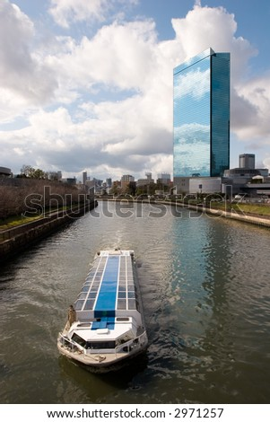 A scenic cruise boat on a river in Osaka Japan with modern building in background.