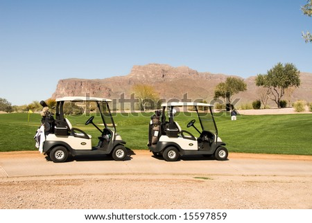 A scenic golf course with two golf carts during a hot summer day