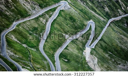A scenic mountain road with hairpins, surrounded by green hills. Stelvio pass, South Tyrol, Italy.