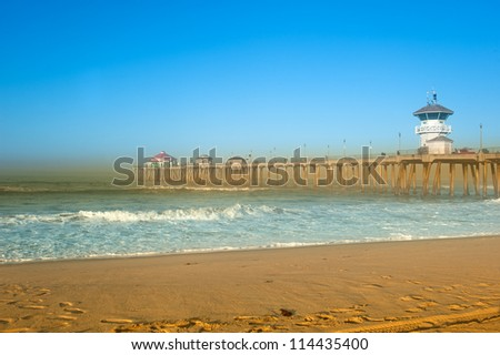 A scenic pier at the beach with smoke from a local fire lining the horizon.