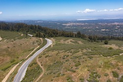 A scenic road meanders through the vegetation-covered hills of the East Bay, just a few miles from San Francisco Bay in Northern California. This area provides open spaces for hikers and bikers.