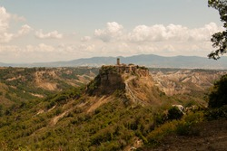 A scenic tufa mountain's view in a Sunny  day with some clouds in the background. Civita di Bagnoregio, a typical medieval italian landscape and the village is the protagonist of the postcard